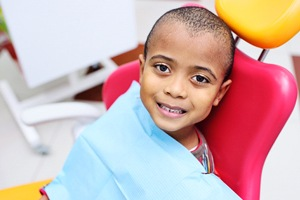 child sitting in a dental treatment chair and smiling