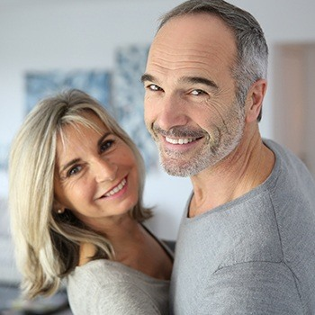 husband and wife smiling in grey shirts