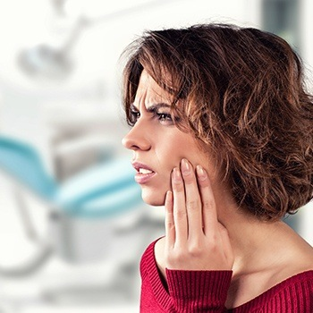 woman holding cheek and jaw in pain