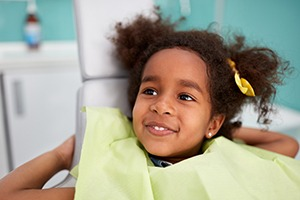 young girl wearing green dental cape